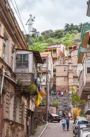 Tbilisi, Georgia - May 03, 2019: Old Tbilisi street view with Kartlis Deda monument on the background. Ordinary people walk the street