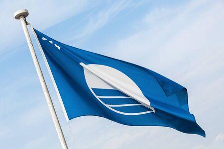 Blue Flag beach. Close-up photo of the flag waving under blue cloudy sky