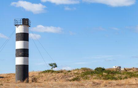 Black and white striped navigational tower located on seaward cliffs on the southwest side of Sevastopol, near Armored Coastal Battery 35, Crimea Фото со стока