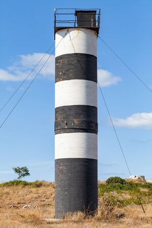 Black and white striped navigational tower located on seaward cliffs on the southwest side of Sevastopol, near Armored Coastal Battery 35, Crimea. Vertical photo