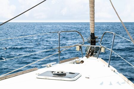 White yacht bow with rolled jib sail and anchor Imagens