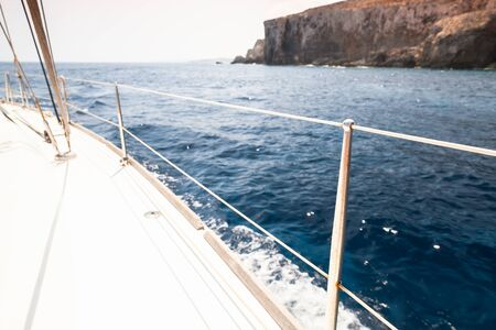 White sailing yacht deck with railings and ropes. Boat trip at sunny summer day