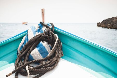 Bow of a small pleasure boat with nautical rope at summer sunny day