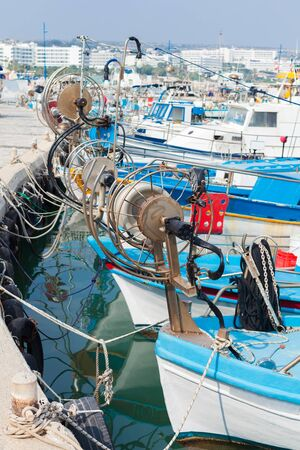Small wooden fishing boats are moored in Ayia Napa, Cyprus island. Vertical photo Stock fotó