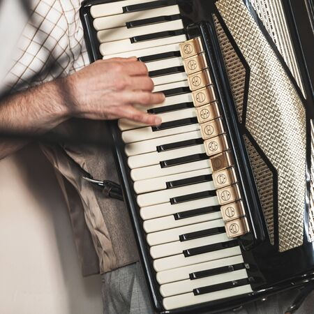 Accordionist plays vintage accordion. Close-up square photo with selective focus