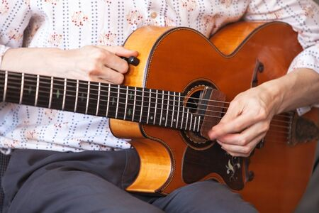 Guitarist tunes vintage acoustic guitar, close-up photo with selective focus on hands