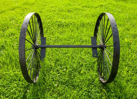 Vintage black metal wheels on one axis stand on green grass at sunny summer day, front view 스톡 콘텐츠