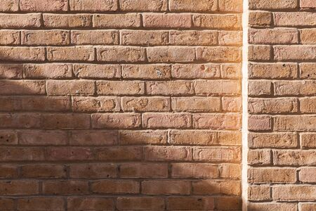 Yellow brick wall with sunlight and shadow on it, frontal view, background photo texture