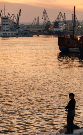 Varna, Bulgaria - July 16, 2014: Woman fisherman stands on a breakwater in Varna port at sunset. Vertical photo Redactioneel