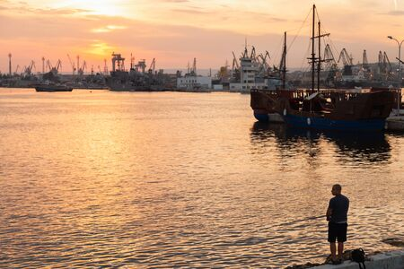 Varna, Bulgaria - July 16, 2014: Fisherman stands on a breakwater in Varna port at sunset