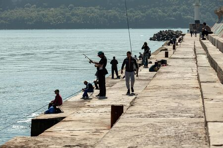 Varna, Bulgaria - September 30, 2014: Fishermen are on the concrete breakwater in Varna port at sunny day, back light silhouette photo