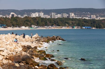 Varna, Bulgaria - September 30, 2014: Fishermen are on breakwater stones in Varna port at sunny day