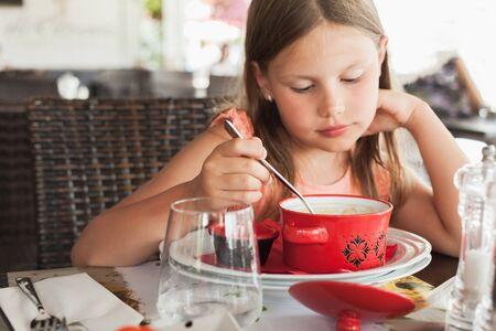 Little blond Caucasian girl eats a soup in a restaurant at summer day, close-up portrait