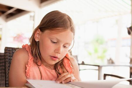 Little blond Caucasian girl reads a menu in a restaurant, close up photo with sleletive focus
