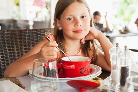 Little blond Caucasian girl with red bowl of a soup sitting in a restaurant at summer day