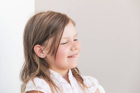Smiling funny blond Caucasian little girl, close-up portrait with closed eyes over gray wall background Banco de Imagens