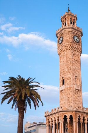 Clock tower and palm tree are under blue sky, it was built in 1901 and accepted as the official symbol of Izmir City, Turkey Imagens