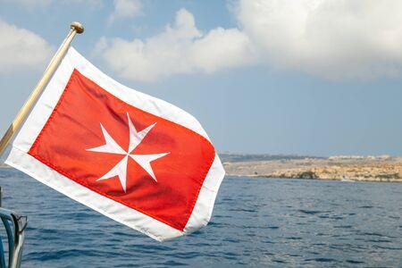 Die Handelsflagge von Malta mit weißem Malteserkreuz auf rotem Hintergrund, montiert auf einem Heck der Vergnügungsyacht Standard-Bild