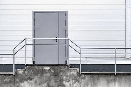 Industrial building facade with gray metal door in white wall