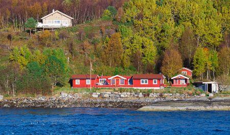 Paisaje costero tradicional noruego, casas de madera roja y graneros en la costa. Sandstad, Hitra, Noruega Foto de archivo