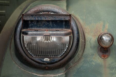 Headlight of a military truck with blackout headlight cover on it, old-timer vehicle from WWII period. Close up photo