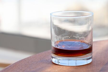Spiced dark Caribbean rum in a glass stands on a wooden table at sunny summer day. Popular drink of Dominican Republic