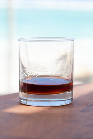 Glass of spiced dark Caribbean rum stands on a wooden table at sunny summer day. Popular drink of Dominican Republic. Vertical photo
