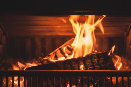 Burning fireplace at night, close-up photo with soft selective focus