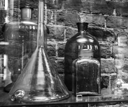 Vintage chemical ware is on the shelf on brick wall background. Black and white photo