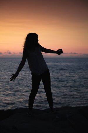 Vertical silhouette photo of happy girl at the sea coast at sunset