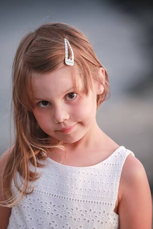 Serious blond little girl in white dress, close-up vertical outdoor portrait
