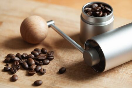 Shiny modern manual coffee grinder and dark roasted coffee beans are on wooden desk, close-up photo with soft selective focus