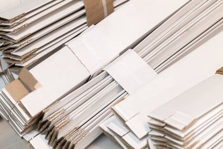 Stacked folded white cardboard boxes, industrial package background photo