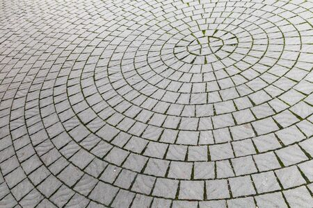 Cobbled road, round pattern of a stone street pavement, abstract background photo texture