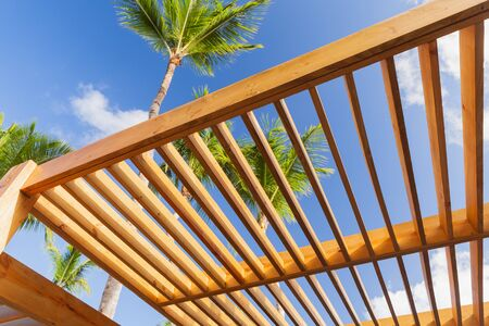 Wooden sunshade roof structure fragment under blue sky at sunny summer day, palm trees are on a background