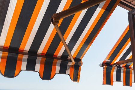 Folding patio balcony awning, side sun shade under bright summer sky