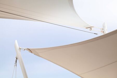 White awnings in sails shape under bright blue sky background Archivio Fotografico