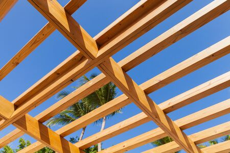 Sunshade roof structure fragment under blue sky at sunny summer day. Wooden planks construction