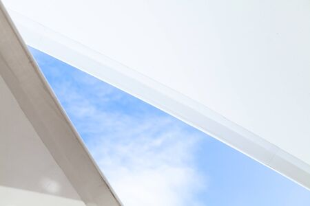White sail shaped awnings are under bright blue sky, abstract background photo