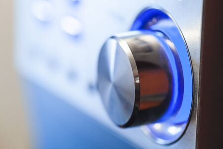Shiny volume control knob with blue LED illumination, close-up photo with selective soft focus