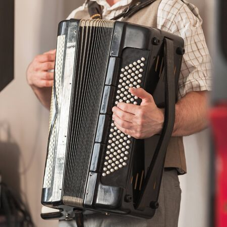 Live music background. Accordionist plays vintage black accordion. Close up square photo