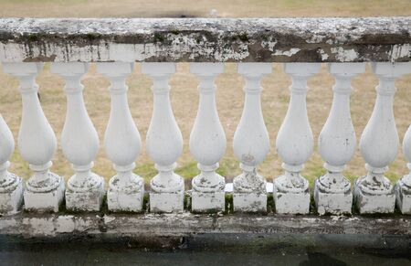 Old terrace balusters made of painted concrete. Abstract classical architecture exterior fragment