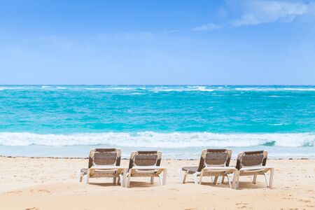 Sunloungers are on sandy beach at sunny day, Dominican Republic