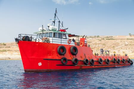 Tug boat with bright red hull goes near Malta island at sunny day