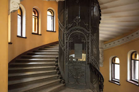 St. Petersburg, Russia - October 25, 2014: The main staircase round interior with forged door of an elevator shaft