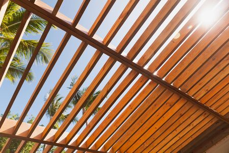 Wooden sunshade roof structure under blue sky at sunny summer day, palm trees are on a background Zdjęcie Seryjne