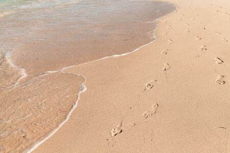 Footprints of bare feet and seawater are on a wet sand of the beach, summer vacation background photo