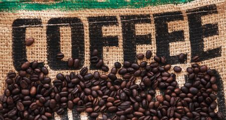 Roasted coffee beans are on jute bag fabric with standard black marking text Coffee. Flat lay photo, top view background  Standard-Bild