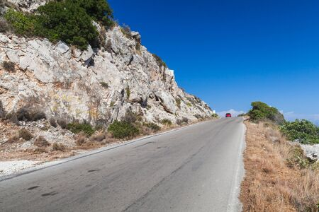 Mountain road perspective view. Travel photo taken at Zakynthos island, Greece. Rural summer landscape Standard-Bild
