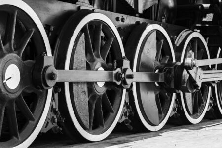 Wheels of vintage steam locomotive with power parts, black and white photo